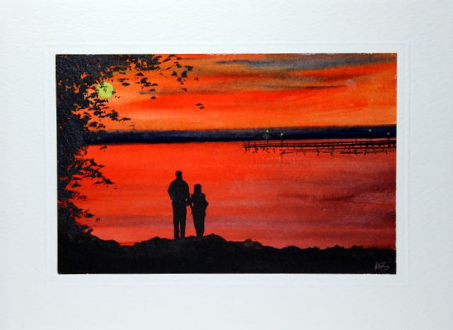 Loving couple stood at the edge of the lake silhouetted by the sun setting