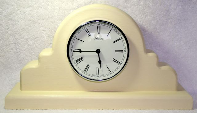 hand made mantle clock made from hard wood and finished in cream, steel rimmed face with Roman numerals and a Westminster chime